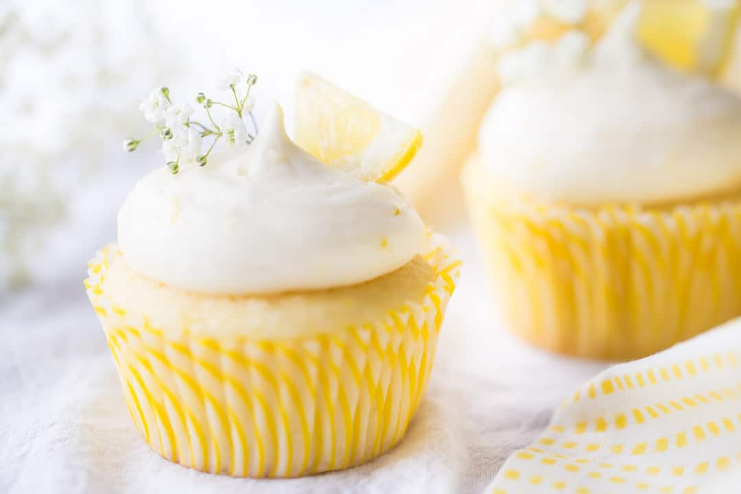 Horizontal image of lemon cupcakes with lemon curd filling & lemon cream cheese frosting, garnished with lemon wedges and a sprig of baby's breath.