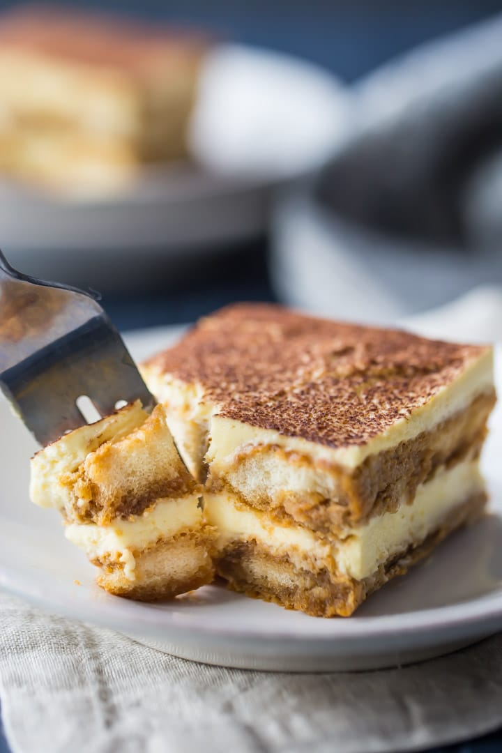 Vertical image of a slice of tiramisu with a fork taking out a bite.