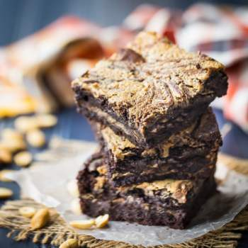 Stack of peanut butter brownies stuffed and swirled with peanut butter, on a blue background with an orange napkin in the background.