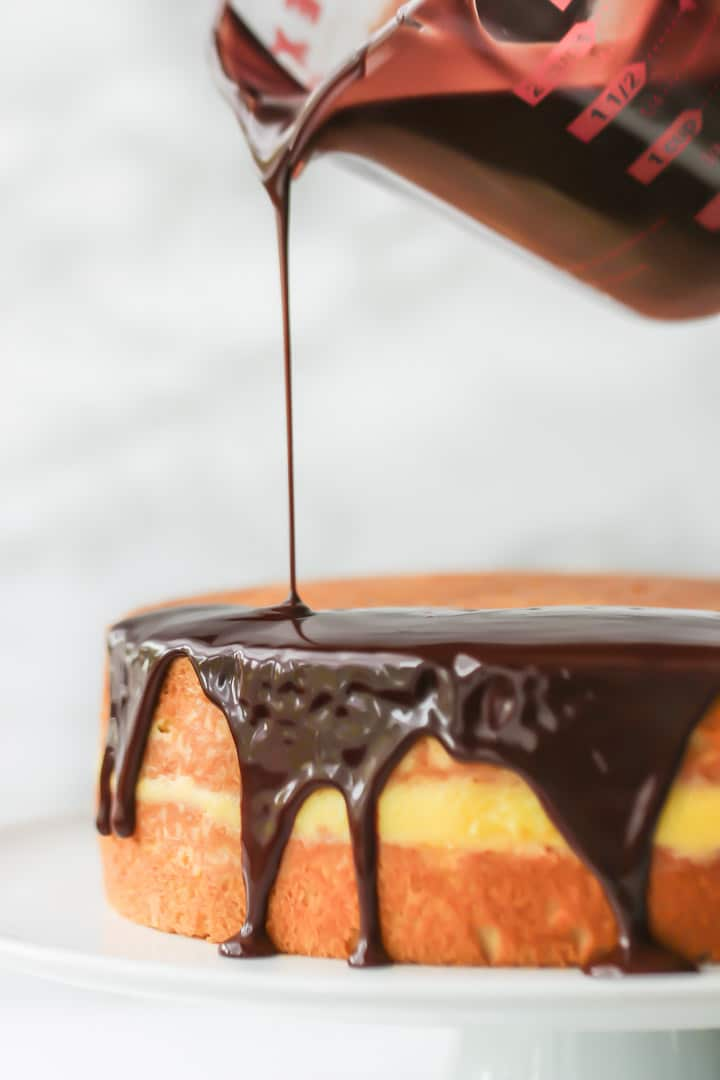 Chocolate topping being poured over vanilla sponge filled with creme patissiere to make classic Boston Cream Pie.