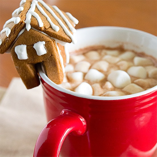 Red mug of homemade hot chocolate with a small gingerbread house on the rim.