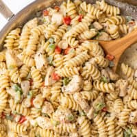 Spoon scooping creamy chicken pasta with bell peppers.