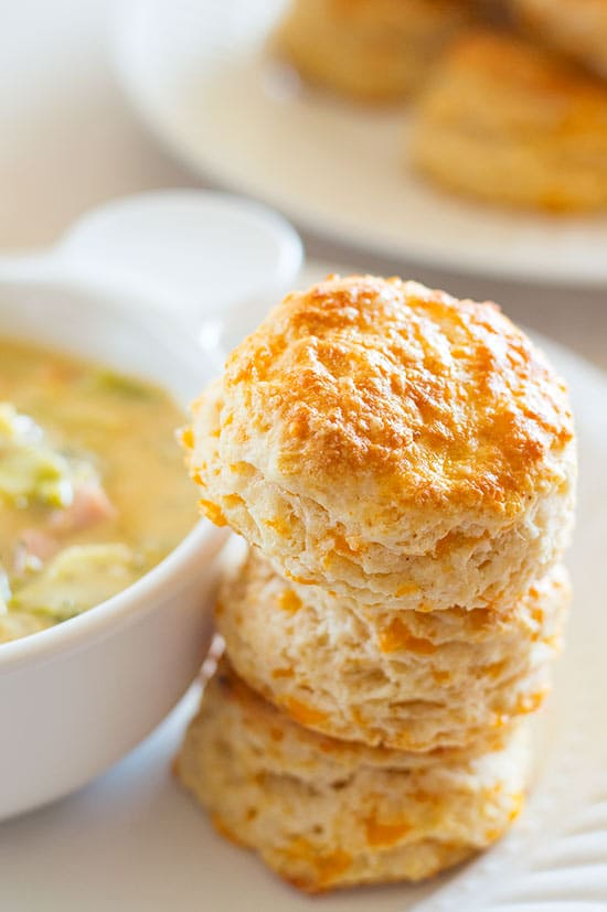 Cheddar Cheese Scones stacked next to a bowl of soup.