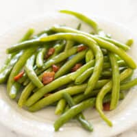 Bacon green beans on a white plate.