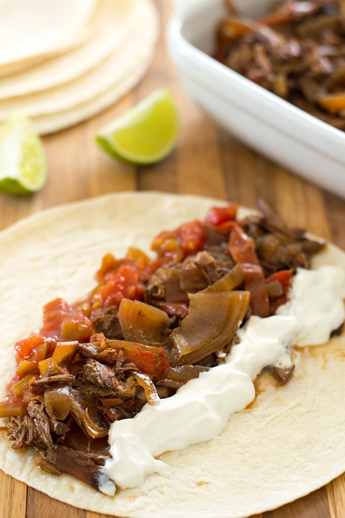 Easy slow cooker beef fajitas on a tortilla with sour cream and salsa.