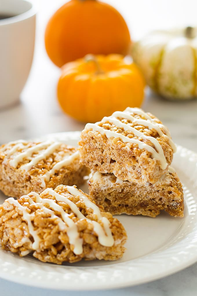 Photo of pumpkin spice rice krispie treats made with pumpkin puree on a white plate.