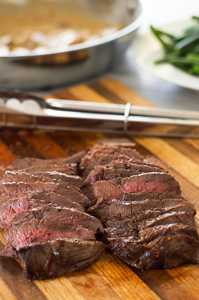 Sliced broiled top sirloin on a cutting board.