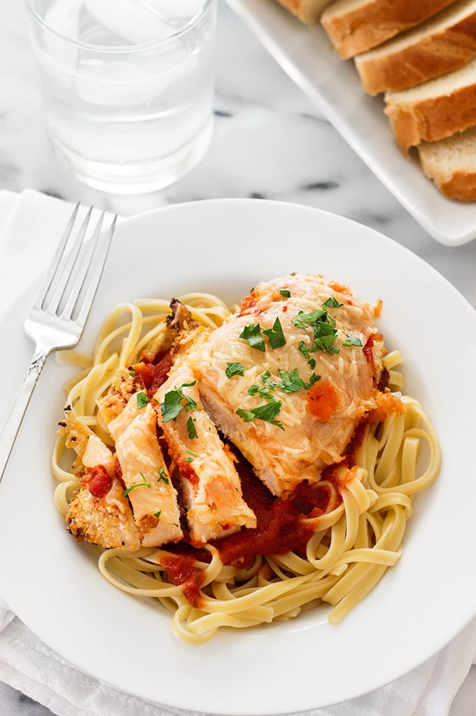 Baked chicken parmesan in a white bowl.