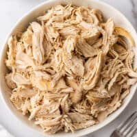 Shredded chicken in a white bowl.