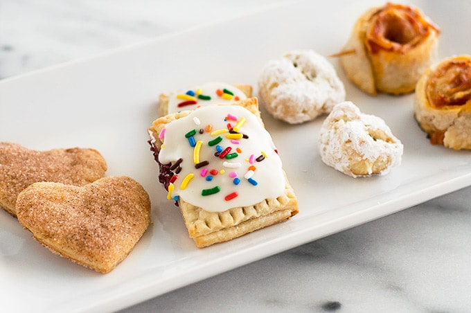 Cinnamon cookies, mini pop tarts, chocolate-stuffed cookies, and pizza roll ups, all made with leftover pie dough on a plate.