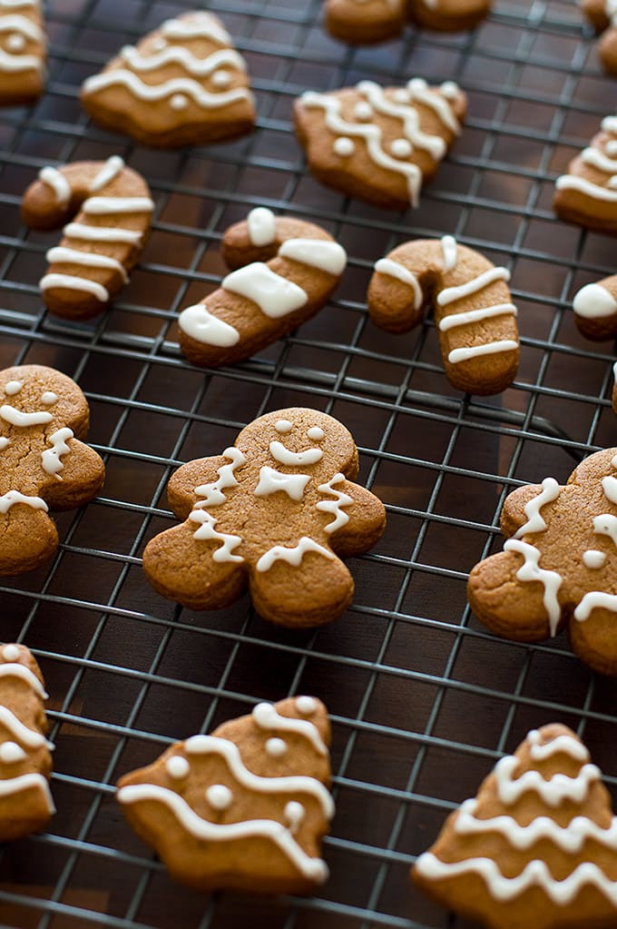 Decorated mini gingerbread cookies on a baking rack.