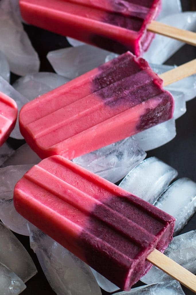 Close up photograph of pink and purple fruit smoothie popsicles on a cookie sheet filled with ice.