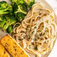 Fettuccine alfredo for one on a plate with broccoli and garlic bread.