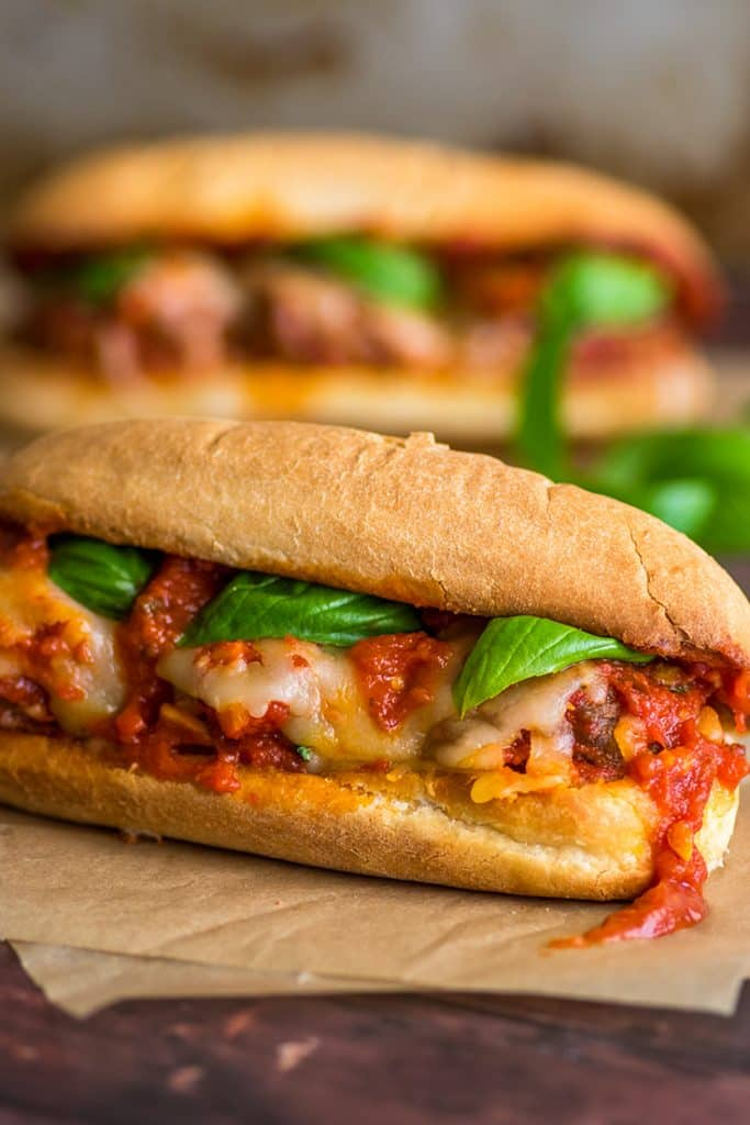 Meatball sandwiches with marinara sauce on parchment paper.