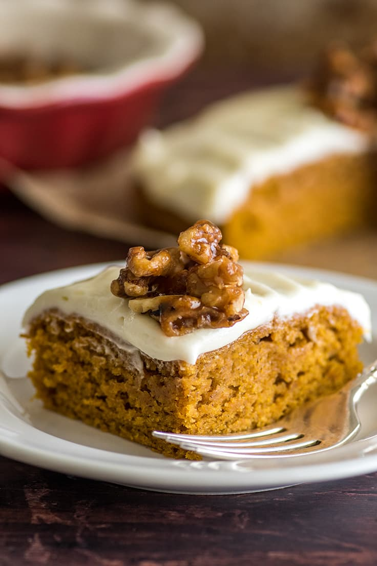 Slice of Mini Pumpkin Cake with cream cheese frosting and candied walnuts.