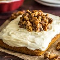 Mini pumpkin cake with cream cheese frosting with candied walnuts piled on top.
