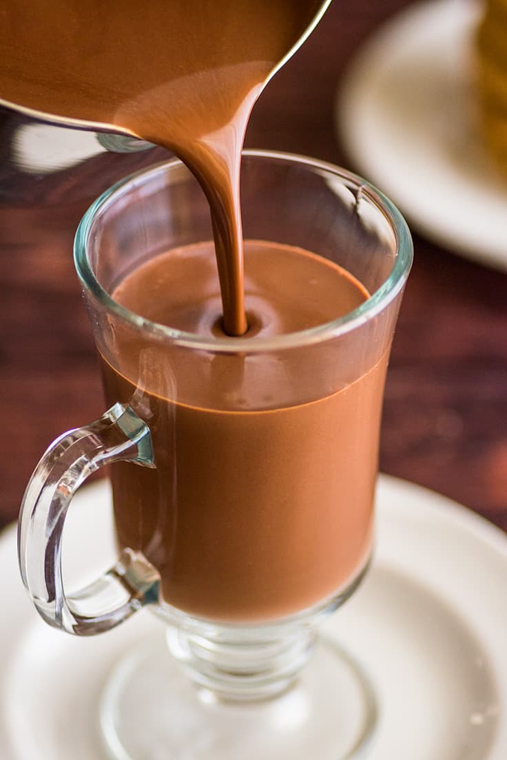 Thick hot chocolate being poured into a glass mug.