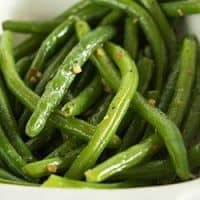 Butter and garlic green beans in a white dish.