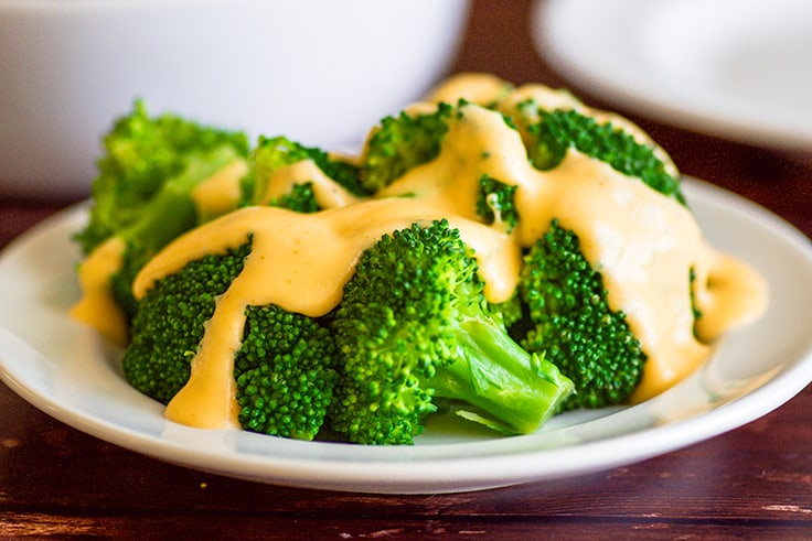 Wide photo of cheese sauce poured over broccoli.