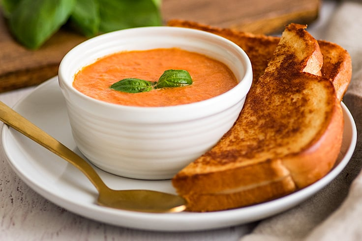 Photo of Creamy Tomato Soup Recipe for Two with grilled cheese sandwich on the side.