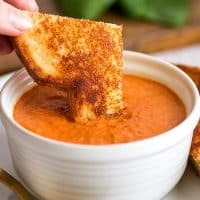 Square photo of grilled cheese sandwich being dipped in Creamy Tomato Soup Recipe for Two.