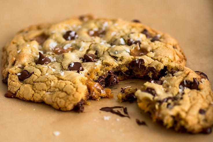 Photo of One Caramel and Sea Salt Chocolate Chip Cookie for Two on parchment paper.