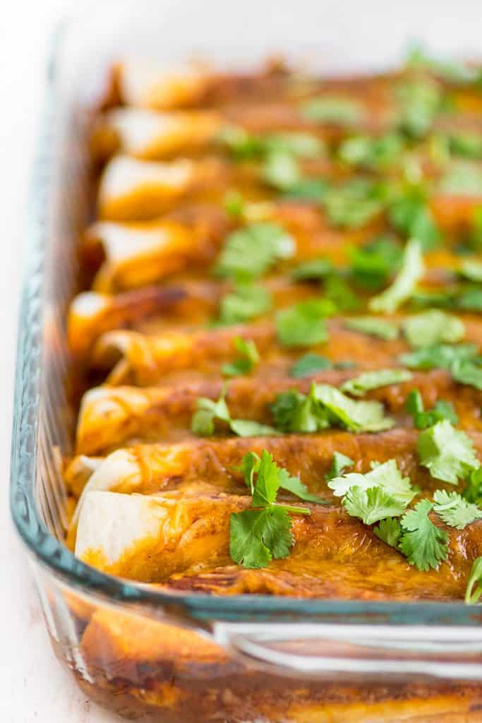 Photo of Carnitas Enchiladas in a pan sprinkled with cilantro.