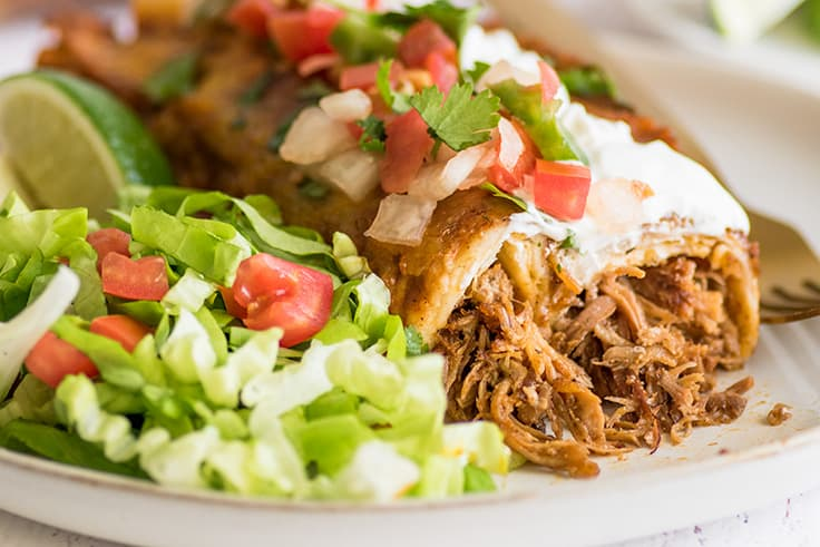 Wide photo of pulled pork enchiladas with carnitas, sour cream, and pico de gallo.