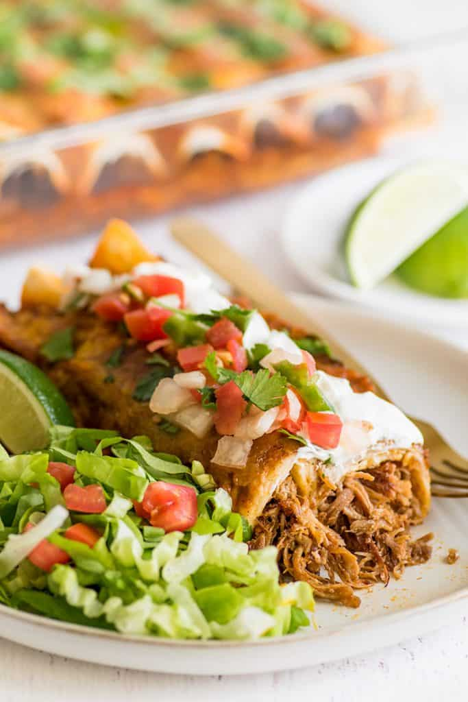 Picture of carnitas enchiladas with pulled pork, sour cream, and pico de gallo.