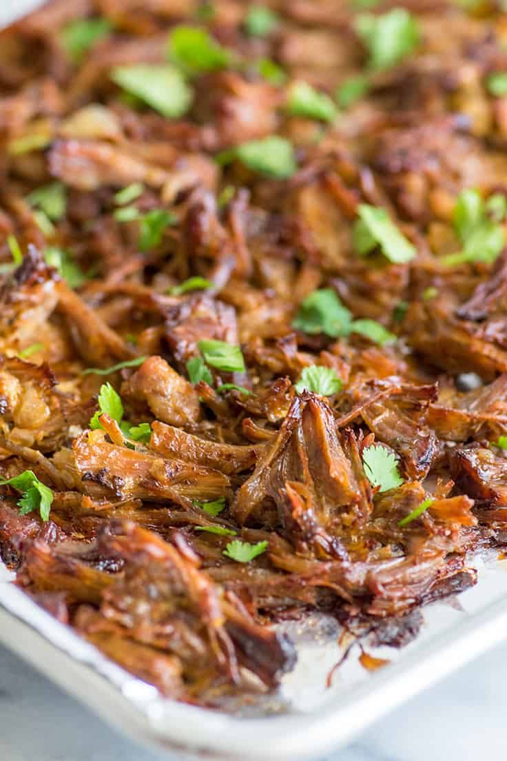 Photo of this easy carnitas recipe shredded and crisped on a baking sheet.