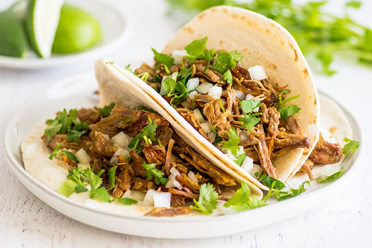 Three classic carnitas tacos, pork tacos with cilantro and diced onion.
