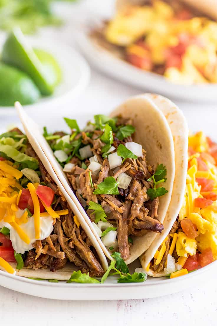 Three different types of carnitas tacos on a plate.
