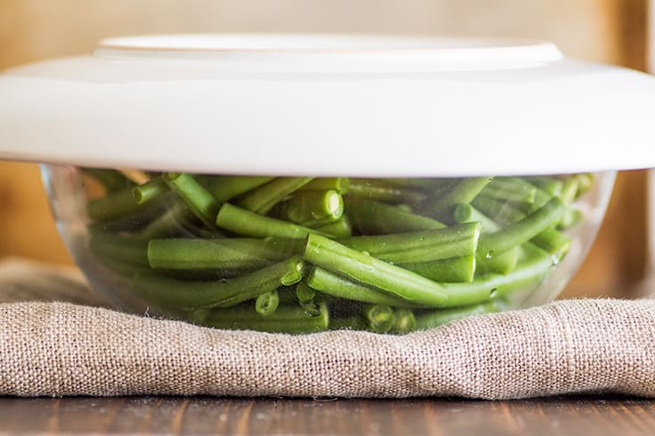 Image of How to Steam Green Beans in the Microwave step 2, green beans in a bowl covered with a plate.