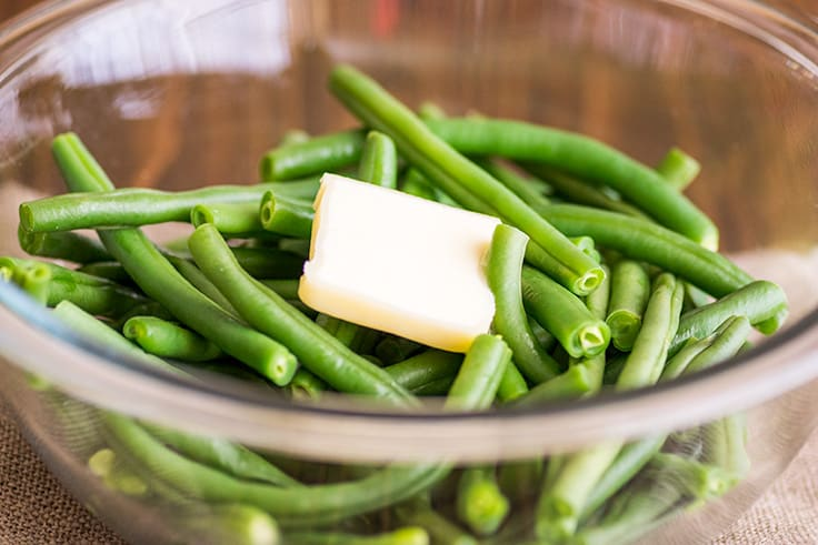 Image of How to Steam Green Beans in the Microwave step 3, green beans in a bowl with tab of butter.