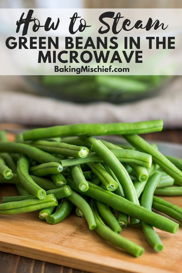 Fresh green beans on a cutting board with text overlay: How to Steam Green Beans in the Microwave.