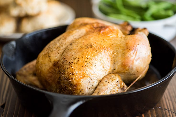 Photo of a whole roasted chicken cooked in a cast iron pan.
