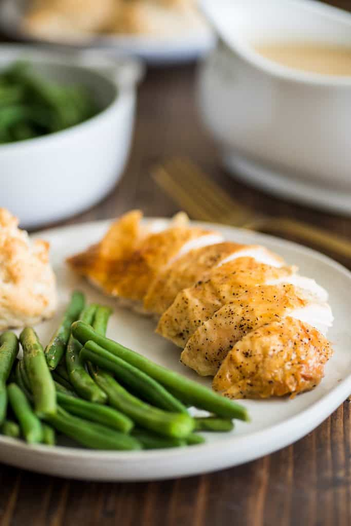 Roasted chicken breast sliced on a plate with green beans.
