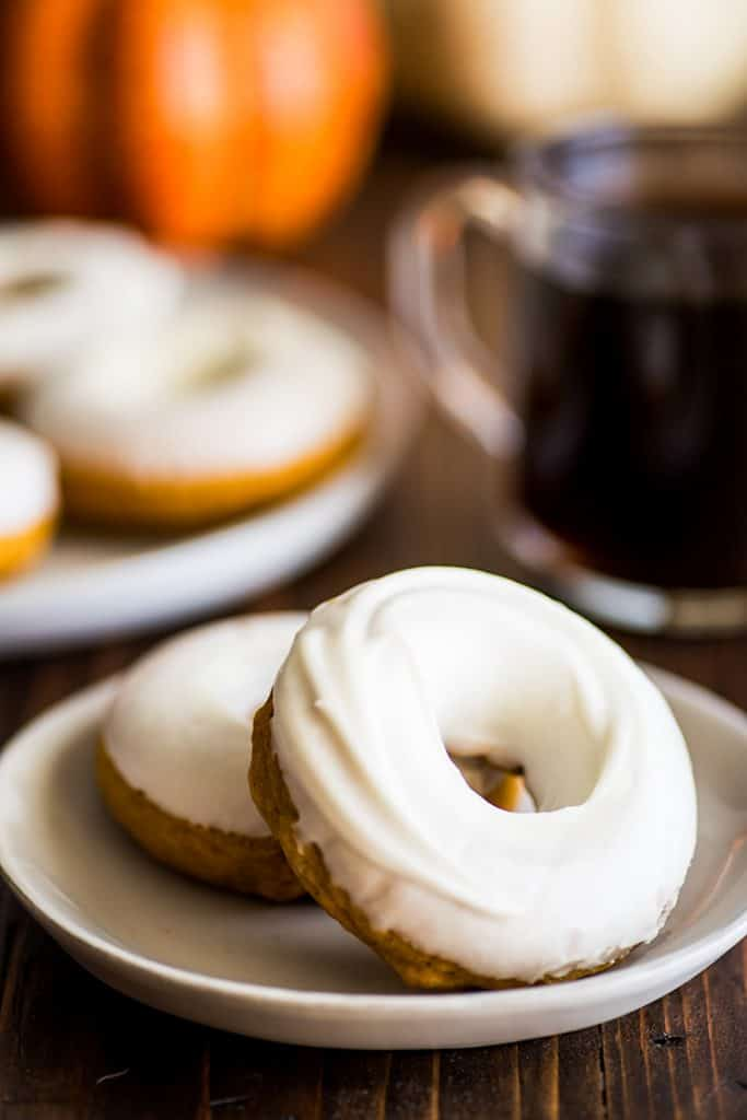 Photo of two Pumpkin Donuts With Cream Cheese Glaze on a plate.