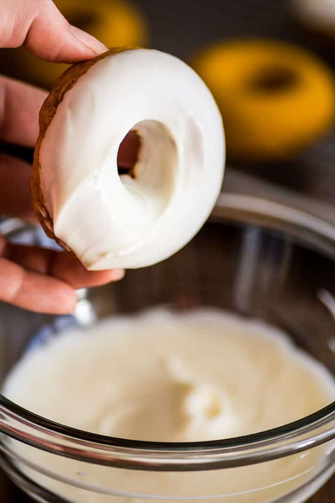 Photo of a baked pumpkin donut being dipped in cream cheese glaze.