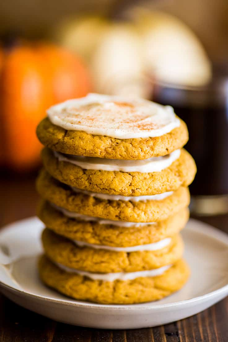 Stack of 6 Small-batch Pumpkin Cookies with Cream Cheese Frosting on a white plate.