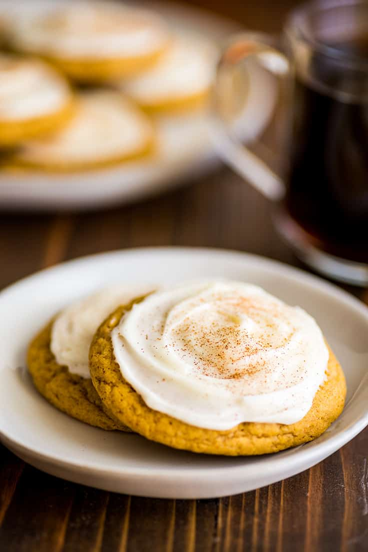 Two pumpkin cookies with cream cheese frosting on a white plate.