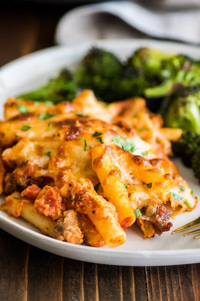 Photo of easy baked ziti on a plate with oven-roasted broccoli.
