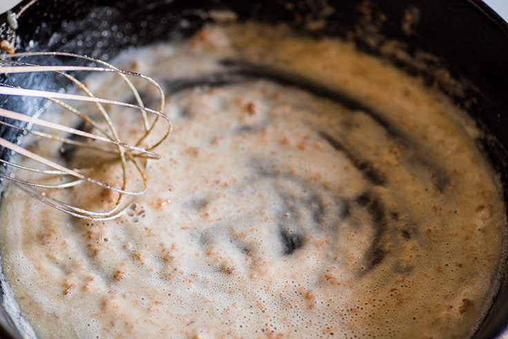 Photo of How to Make Gravy From Drippings step 3: flour being whisked into browned pan drippings.