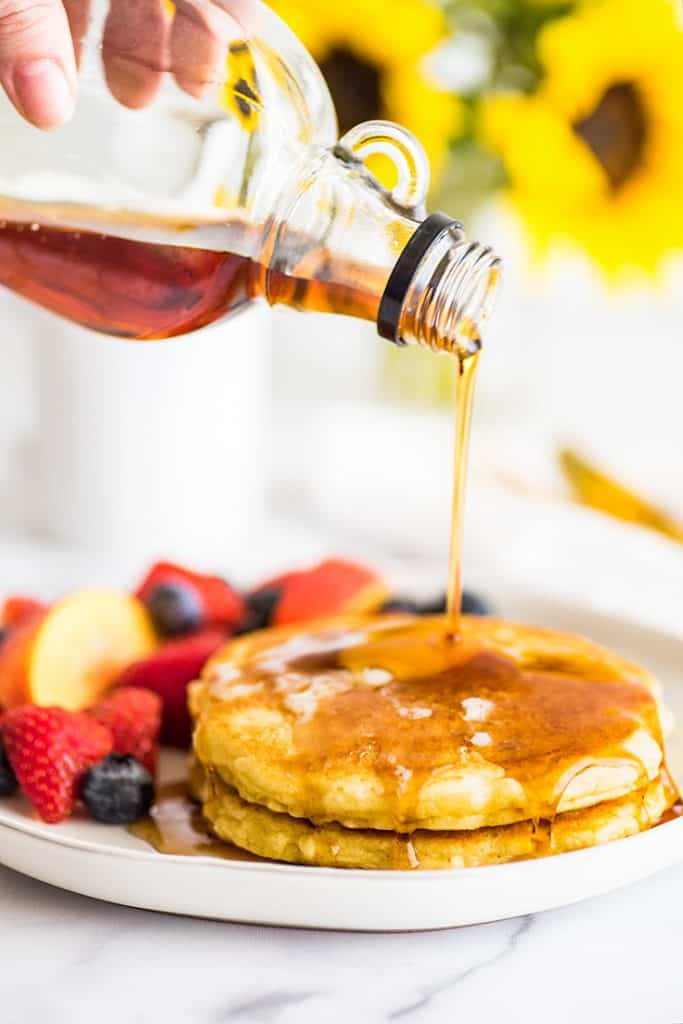 Picture of syrup being poured over two pancakes.