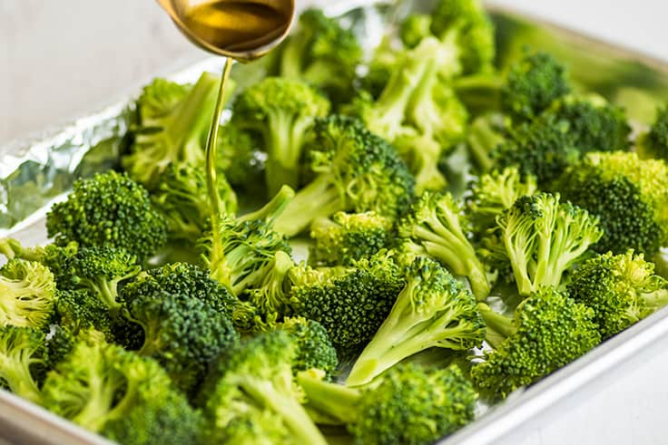 How to Cook Broccoli in the Oven Photo of olive oil being drizzled over broccoli.