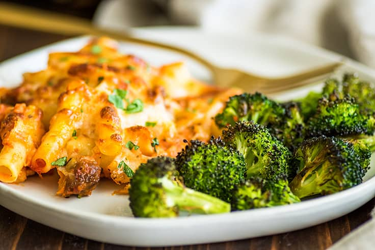 Image of crispy oven-roasted broccoli on a plate with baked ziti.