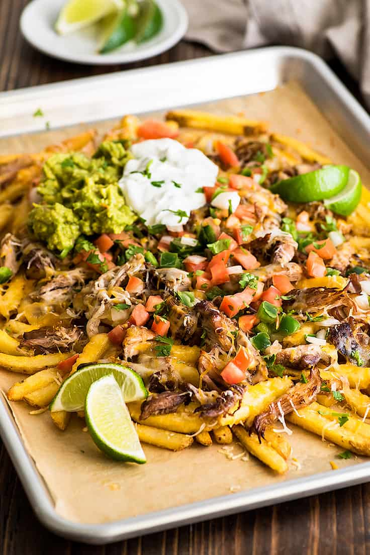 Image of Carnitas Nacho Fries on a baking sheet with sour cream and guacamole.