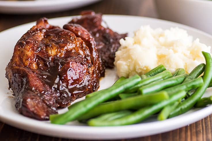 Picture of baked country-style pork ribs on a plate with green beans and mashed potatoes.