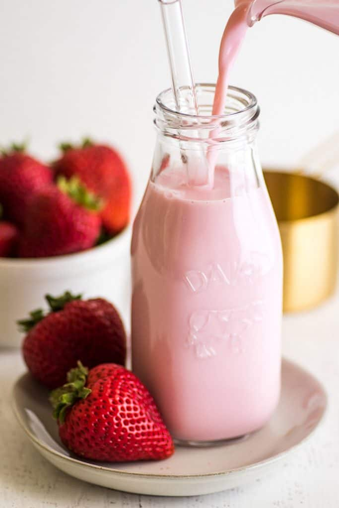 Photo of Homemade Strawberry Milk for One being poured into a glass bottle.