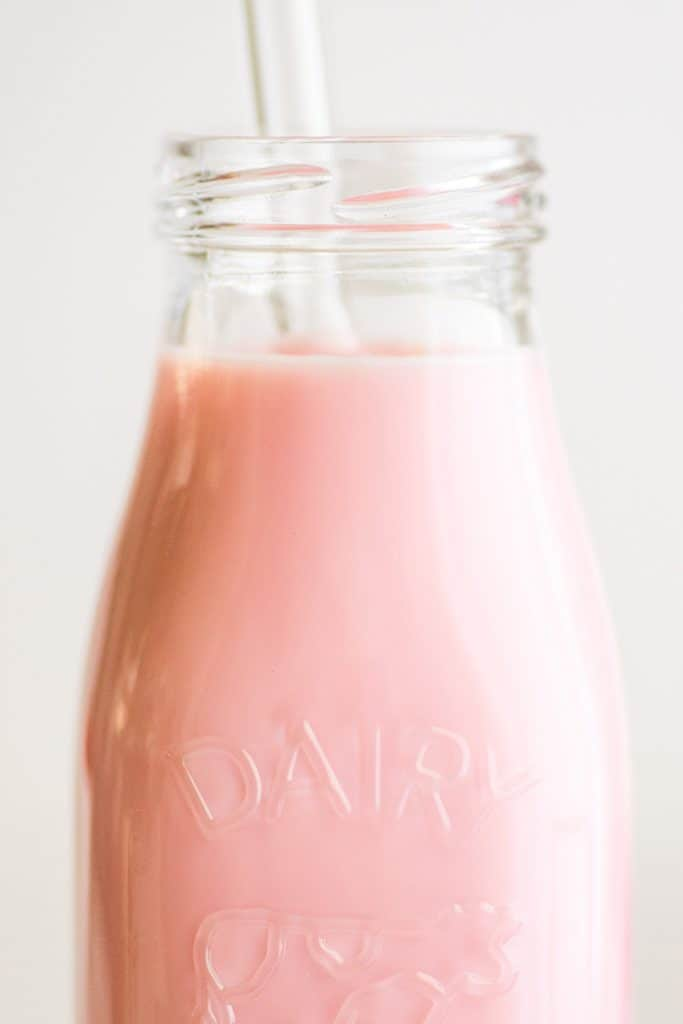 Close up image of easy homemade strawberry milk in a glass jar.